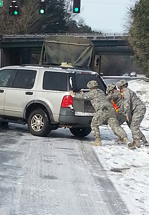 National Guardsmen push a car