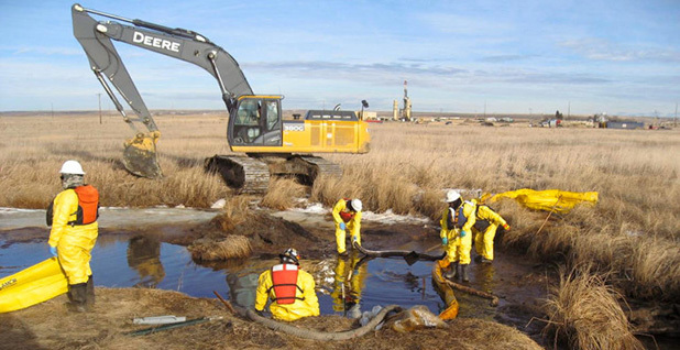 Workers clean up a spill of oilfield waste