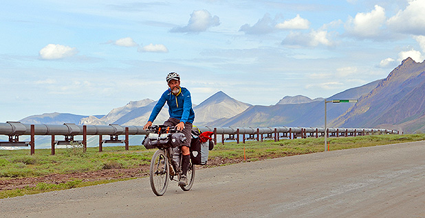 Cyclists along Dalton highway next to Trans-Alaska pipeline. Photo credit: Margaret Kriz Hobson/E&E News