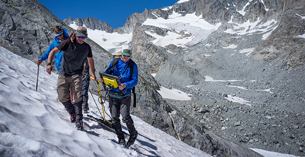 Researchers pull ground penetrating radar across a permanent snowfield at the edge of the Dinwoody Cirque. Photo: Ben Storrow