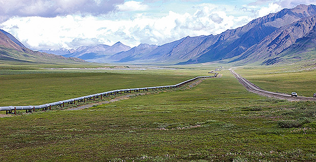 A pipeline follows a green valley in Alaska with mountains in the background. Photo credit: USGS.