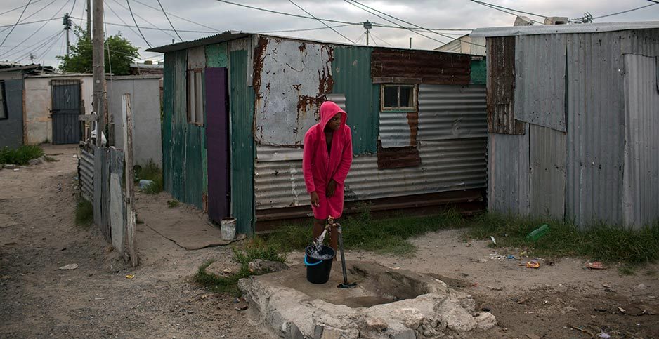 A woman in red stands near a water tap in an impoverished settlement of shacks. Photo credit: Halden Krog/Associated Press