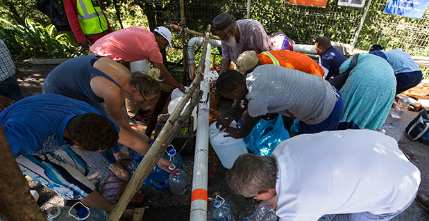 Residents lean over to collect water from a thin pipe in Cape Town. Photo credit: Halden Krog/Associated Press