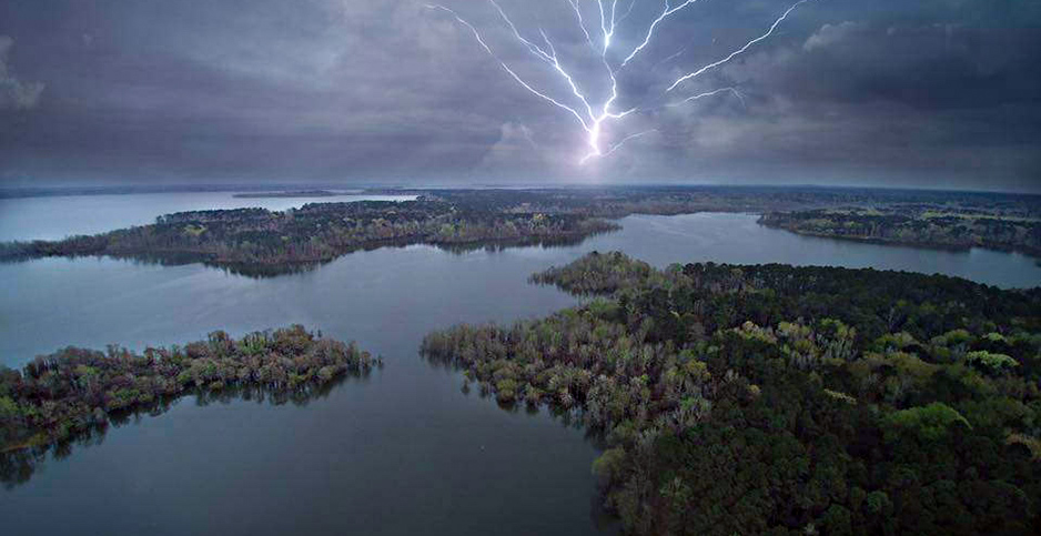 A lightning strike is visible in dark clouds with a forest-lined lake in the foreground. Photo credit: lawepw/Flickr