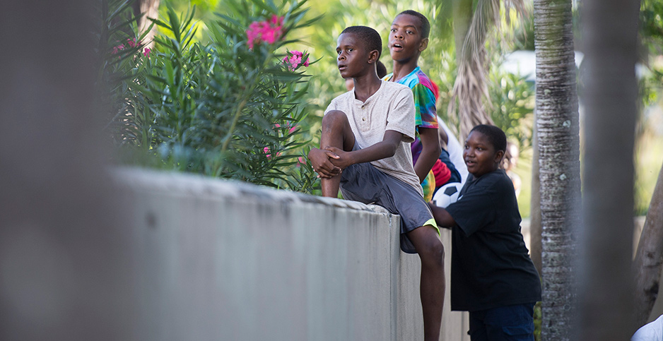 Three children sit on a white wall after being evacuated from the Island of Barbuda. Photo credit: Victoria Jones/PA Wire/Associated Press