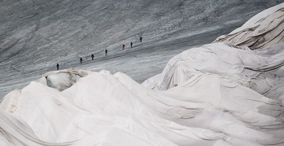 A portion of the Rhône Glacier in Switzerland is covered in blankets to prevent it from melting, with a line of people walking in the background. Photo credit: Urs Flueeler/Keystone/Associated Press