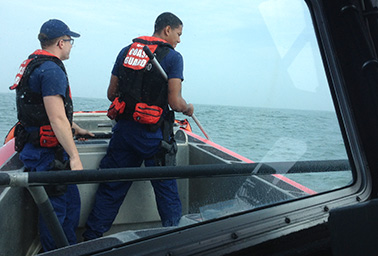 U.S. Coast Guard law enforcement crew members on a boat. Photo credit: Nathanial Gronewold/E&E News