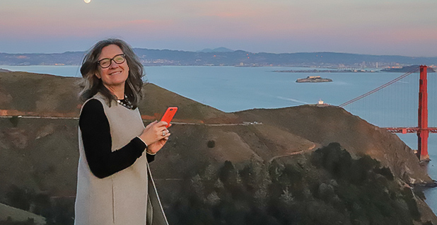 Dominique Browning holds her phone on a hill with a bridge in the background. Photo credit: Jeremy Symons.