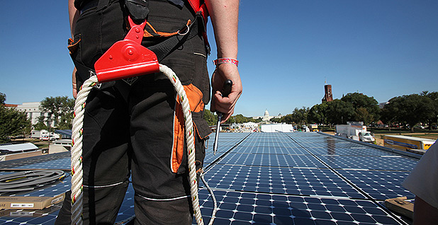 Student wearing rope equipment looking at solar panels on National Mall. Photo credit: Department of Energy Solar Decathlon/Flickr