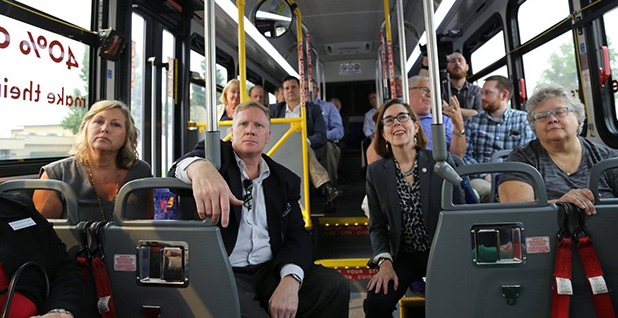 Oregon Gov. Kate Brown (D), sitting in a packed bus, looking at the camera. Photo credit: Gov. Kate Brown/Facebook.
