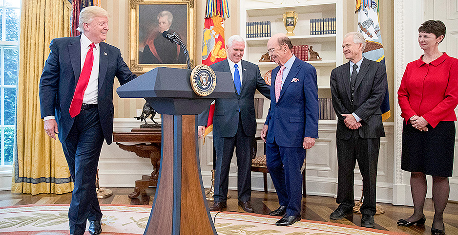 President Trump gestures as he walks away from a lectern with Vice President Mike Pence, adviser Peter Navarro and others looking on. Photo credit: Andrew Harnik/Associated Press