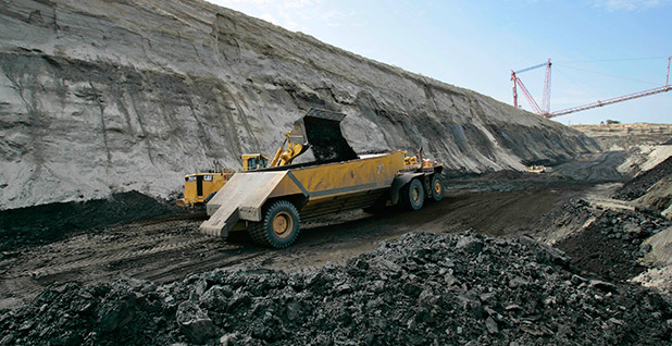 A yellow truck is seen on a narrow gravel road in an open pit coal mine. Photo credit: David J. Phillip/Associated Press