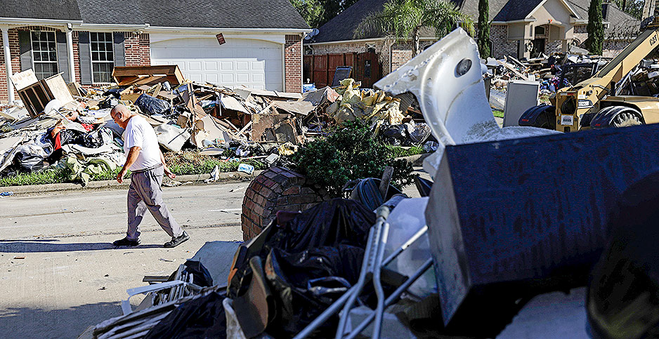 A man walking along a street lined with piles of debris after Hurricane Harvey struck parts of Texas last summer. Photo credit: David Goldman/Associated Press
