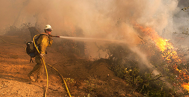Firefighter pointing hose at fire. Photo credit: Kari Greer/U.S. Department of Agriculture/Flickr