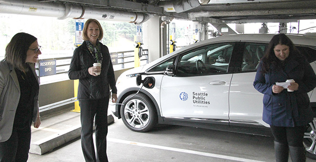 Seattle Mayor Jenny Durkan stands in front of an electric car holding a coffee. Photo credit: Jenny Durkan/Facebook