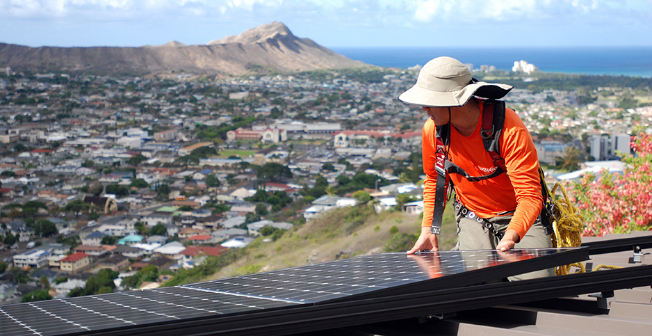 Dane Hew Len, lead installer for RevoluSun, places a solar panel on a roof in Honolulu. Photo credit: Cathy Bussewitz/Associated Press