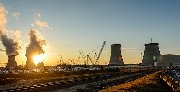 The sun sets behind the Vogtle 1 and 2 cooling towers near the units 3 and 4 construction site. Photo credit: Georgia Power Co.