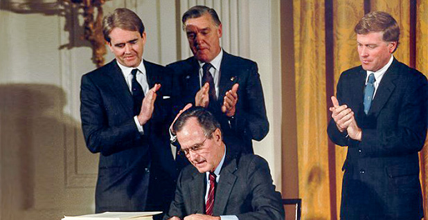 Then-EPA Administrator William Reilly (left) watches as President George H.W. Bush signs the 1990 Clean Air Act Amendments. Photo credit: Carol T. Powers/EPA