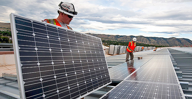 Workers install solar panels. Photo credit: Dennis Schroeder/National Renewable Energy Laboratory
