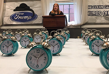Madeline Page, sits behind alarm clocks on a table. Photo credit: Maxine Joselow/E&E News