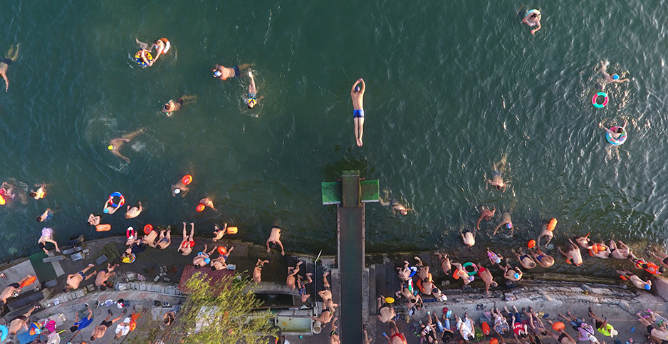Residents of Xiangyang city, China, are pictured swimming in a river to escape the heat. Photo credit: Imagine China/Newscom