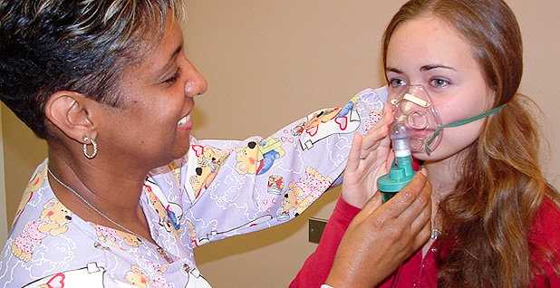 Nurse holds mask over patient's face. Photo credit: EPA
