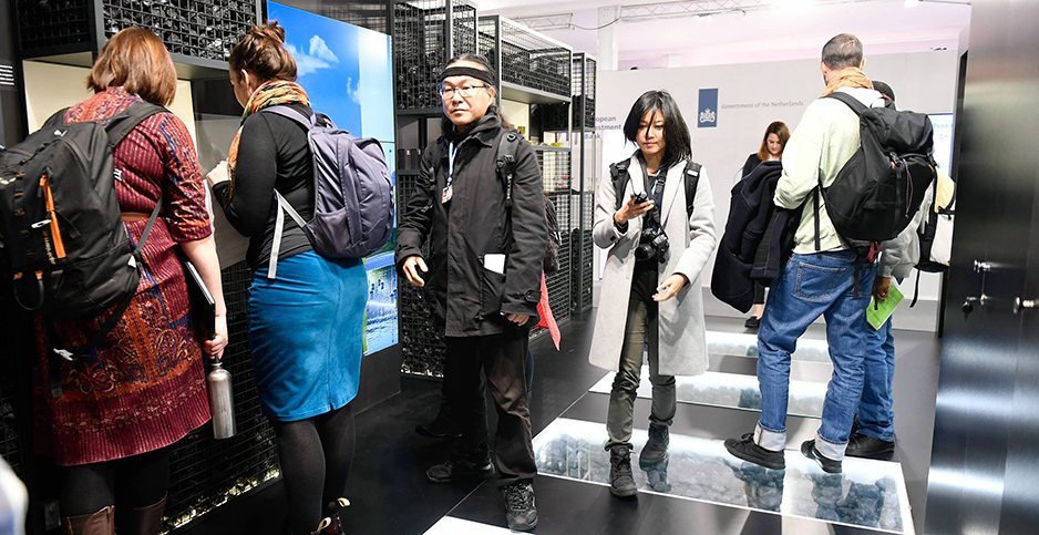 Visitors to the UN climate conference in Poland walk among coal exhibits.  Photo credit: Photopqr/Ouest Fance/MAXPPP