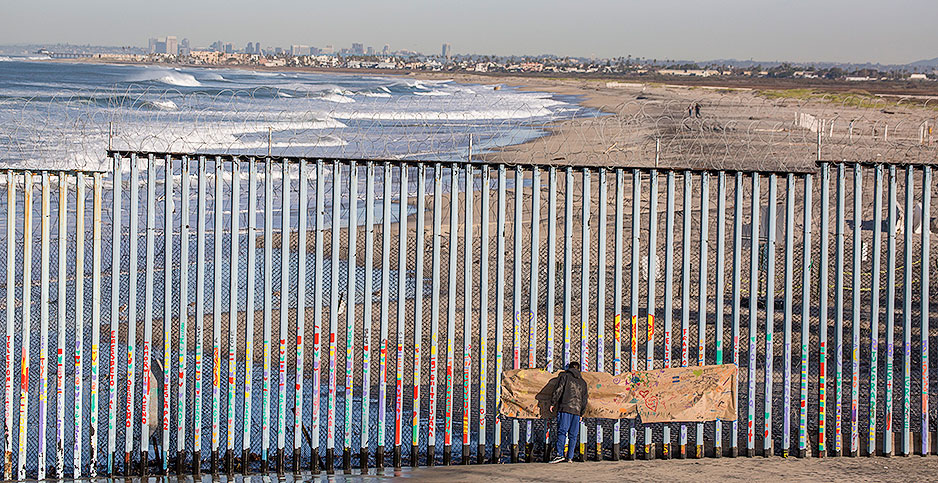 A man in Tijuana, Mexico, looks through the border fence toward the United States. Photo credit: Omar Martinez/dpa/picture-alliance/Newscom