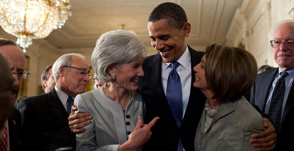 President Obama embraces Secretary of Health and Human Services Kathleen Sebelius (left) and House Speaker Nancy Pelosi. Photo credit: Barack Obama Presidential Library