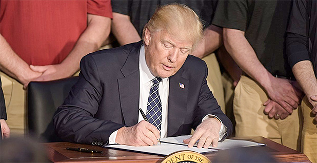 Trump signing executive order. St. Louis
