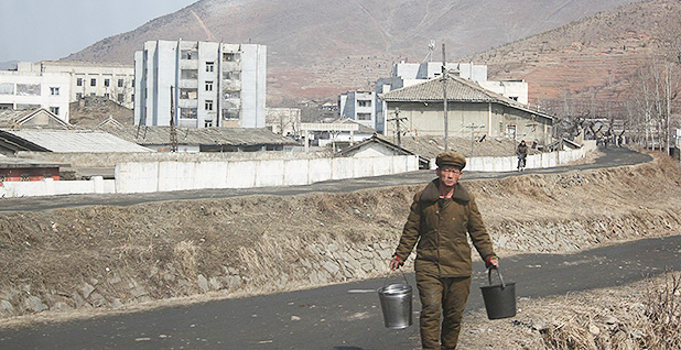 Man carries water in North Korea. Photo credit: Margaret Palmer