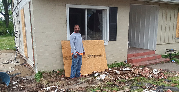 Johnny Bobo in front of his damaged home. Photo credit: Thomas Frank/E&E News