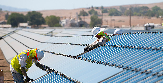 Workers install solar photovoltaic panels. Photo credit: First Solar Inc.