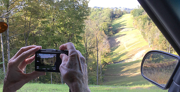 Bill Hughes shows a visitor pipeline construction on steep terrain. Credit: Mike Soraghan/E&E News