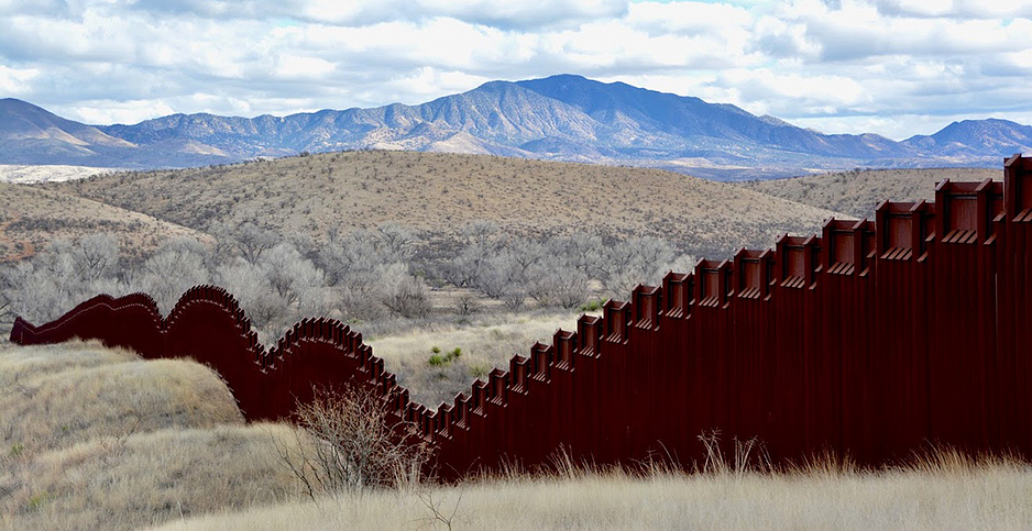 Border wall with mountains in distance. Photo credit: Avery Ellfeldt/E&E News