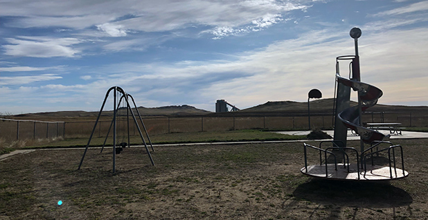 A coal silo at the Eagle Butte mines is seen from a playground in the Rawhide subdivision in early October. Photo credit: Benjamin Storrow/E&E News