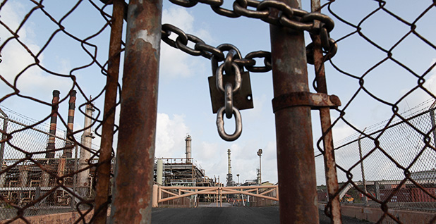 The petroleum refinery is seen behind a locked gate. Photo credit: Alvin Baez/REUTERS/Newscom