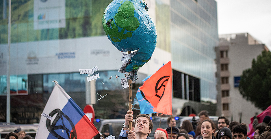 An activist holds a broken globe in protest. Photo credit: Brais G. Rouco/SOPA Images/Sip/Newscom
