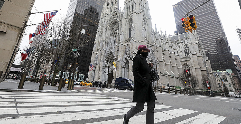 A woman wearing a face mask walks past St. Patrick's Cathedral on 5th Avenue in New York City last week. Photo credit: CHINE NOUVELLE/SIPA/Newscom