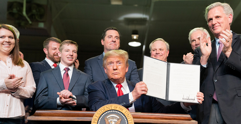President Trump holding up memorandum signature with people standing behind him. Photo credit: Shealah Craighead/White House/Flickr