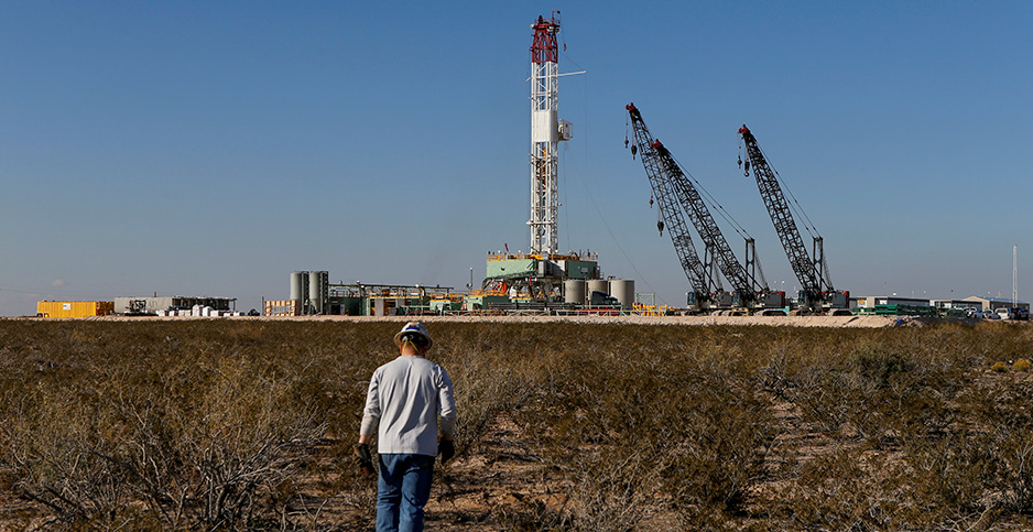 Oil worker and drilling rig in Texas. Photo credit: Angus Mordant/REUTERS/Newscom