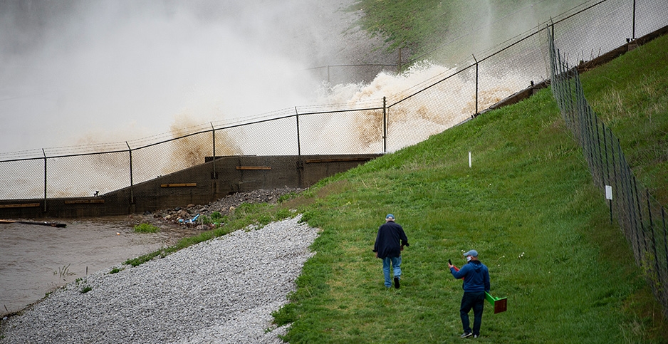 People walk next to a dam with water gushing behind a fence. Photo credit: Kaytie Boomer/The Bay City Times/Associated Press