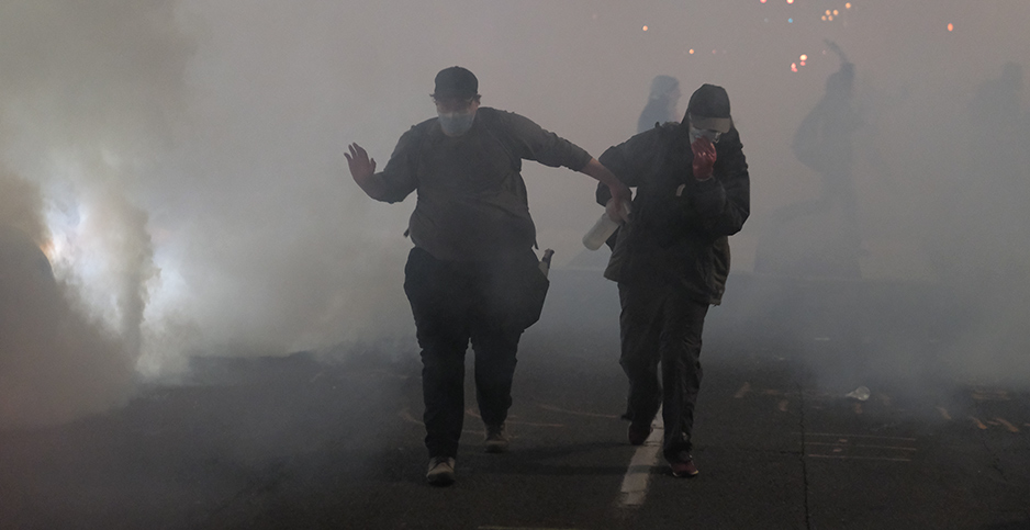 Protesters run from tear gas and flash bang grenades in Portland, Ore. Photo credit: Alex Milan Tracy/Sipa USA/Newscom