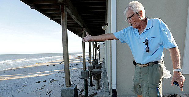 Ivan Juric looks at his damaged beach home. Photo credit: Charlie Riedel/Associated Press