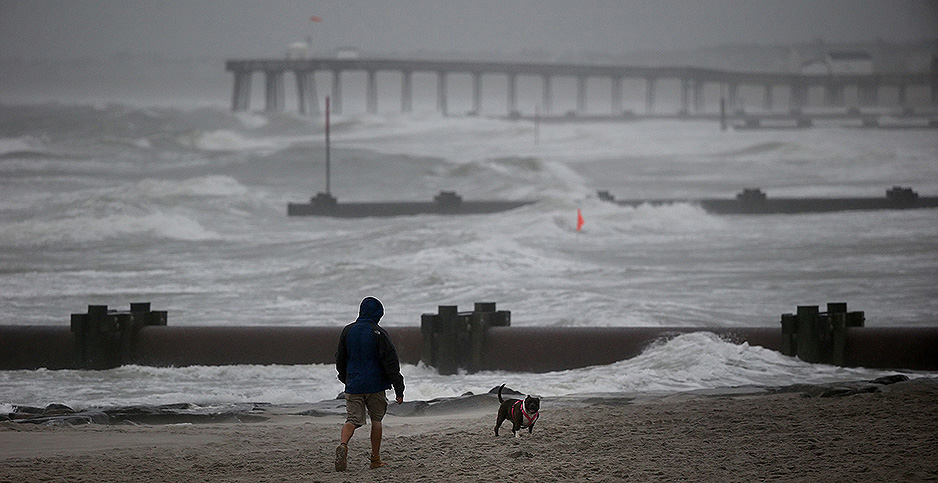 A man walks his dog on the beach as Tropical Storm Isaias reaches Ocean City, N.J. Photo credit: David Maialetti/The Philadelphia Inquirer/TNS/Newscom