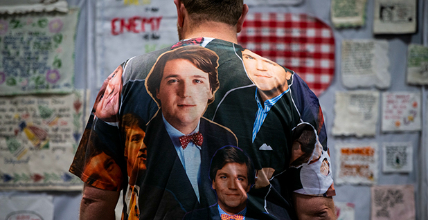 A man in a shirt with Tucker Carlson's face on it. Photo credit: Max Oden/Sipa USA/Newscom