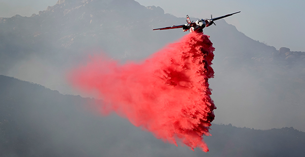 A plane dropping a red plume of fire retardant in the air Photo credit: K.C. Alfred/San Diego Union-Tribune/ZUMA Wire/Newscom