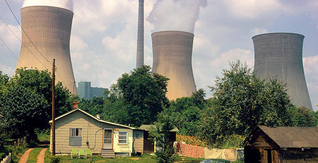 Smokestacks loom over a house. Photo credit: National Archives