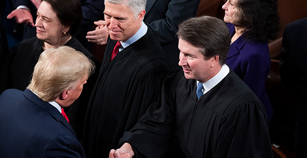 President Donald Trump shakes Justice Brett Kavanaugh's hand, Justices Elena Kagan and Neil Gorsuch in the background. Photo credit: Tom Williams/CQ Roll Call/Newscom
