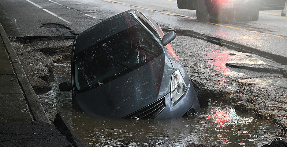 A car lies half-submerged in a Baltimore sinkhole caused by flash flooding in May 2018. Photo credit: Jerry Jackson/Baltimore Sun/TNS/Newscom